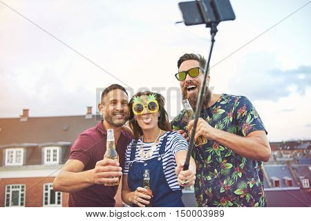 Trio of laughing and drunk friends with selfie stick camera phone taking a picture of themselves drinking beer on top of roof in urban area