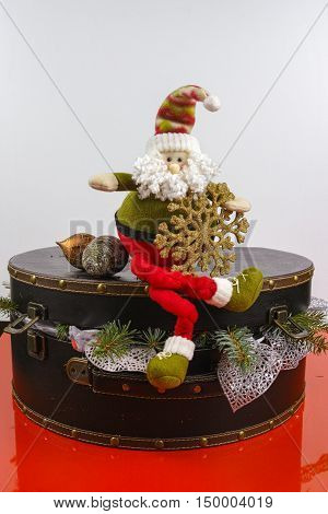 Santa Claus sits on vintage brown coffer with white Christmas tree decoration copy space