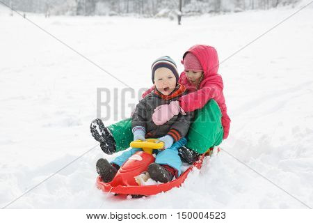 Brother and sister playing in the snowy winter landscape hugging sledding having winter fun. Active family lifestyle bonding natural childhood fun and carefree childhood concept.
