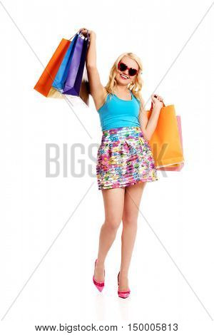 Happy woman in sunglasses holding shopping bags