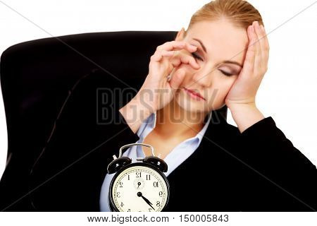 Tired business woman behind the desk with alarm clock