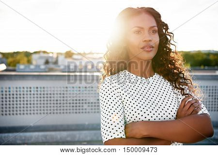 Confident young woman standing on an urban rooftop daydreaming with her arms folded backlit by the bright flare of the rising sun