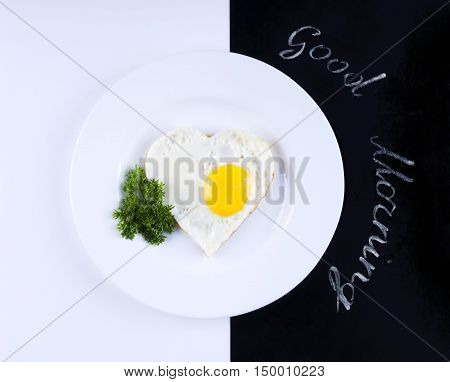 Scrambled eggs in a heart shape on a black and white background. Scrambled eggs for breakfast. Written good morning.