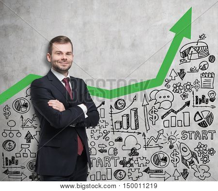Smiling businessman in red tie standing near concrete wall with green arrow and startup sketch on it. Concept of small business. Mock up