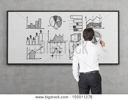 Rear view of businessman in white shirt drawing graphs on whiteboard. Concept of stats and big data