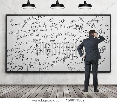 Rear view of man in suit staring at whiteboard with formulas in confusion. Classroom with concrete wall and wooden floor. Concept of exact sciences and studying.