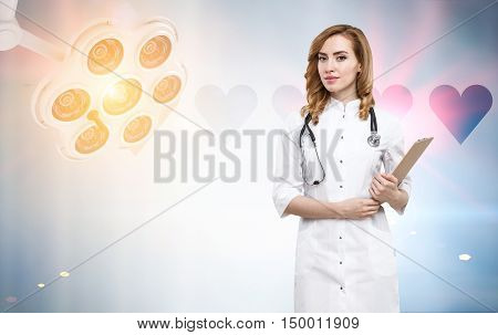 Portrait of gorgeous woman doctor holding a clipboard and standing in room with surgical lamp. Concept of surgical work. Toned image
