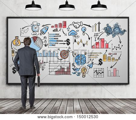 Rear view of businessman with suitcase looking at giant colorful business sketch on whiteboard in room with wooden floor. Concept of bull's eye