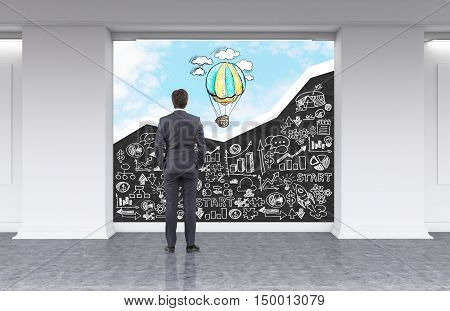 Rear view of man looking at blackboard with white business sketches and sky with hot air balloon in office lobby. Concept of no limits to perfection. 3d rendering. Mock up