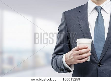 Businessman wearing gray tie and holding paper cuppa coffee is standing in blurred company office. Concept of management. Mockup