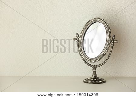 Female mirror on light wall background