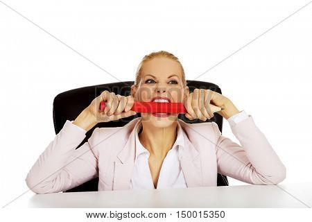 Angry business woman sitting behind the desk and biting huge pen