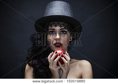 Halloween. Fashion portrait of witch or night vampire woman with red apple. red lips