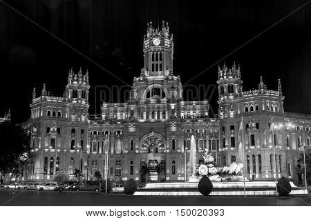 Cybele Palace at the Plaza de Cibeles with light trails of the traffic at night Madrid Spain. Colorful illumination Cybele fountain dark sky. Black and white