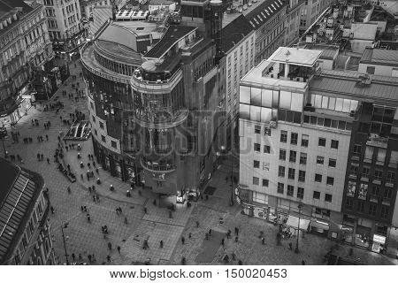 VIENNA AUSTRIA - FEBRUARY 9 2016: Crowd of people at the Stephansplatz. Aerial night view of famous landmark with many shops restaurants bars and modern buildings. Black and white