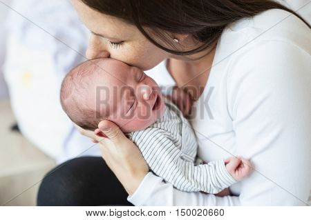 Beautiful young mother with her newborn baby son, sitting on bed in bedroom