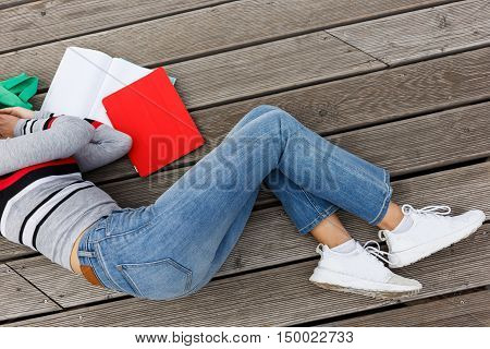 Girl fell asleep with open books on wooden stage on street