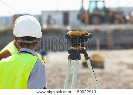 Surveyor engineer at work. Construction site. Land surveying.