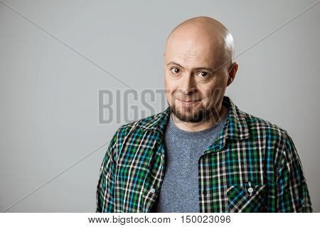 Sincere shy handsome man smiling over beige background. Copy space.