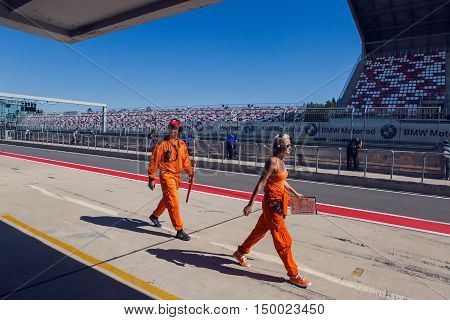 Moscow region, Russia - 27 August : route Moscow raceway technical staff male and female in an orange jumpsuit , the clothes are on the inner track in day of Russian cinema 27 August, 2016.