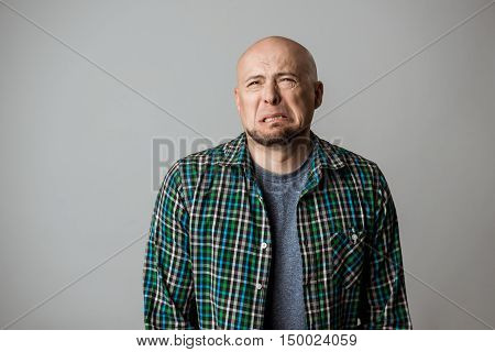 Resentful sad emotive man in shirt posing over beige background. Copy space.