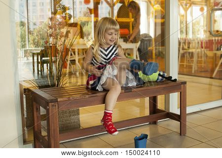 Cuite smiling little girl is putting of rain boots in the playschool