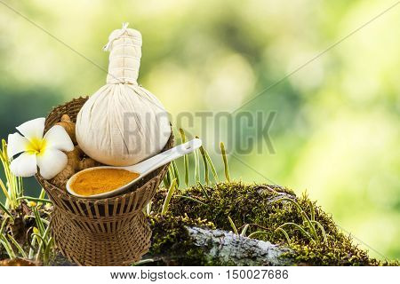 Spa herbal compressing ball , white frangipani flowers (Plumeria spp , Apocynaceae, Pagoda tree, Temple tree) , turmeric powder in white spoon in bamboo basket on moss waterfall on the mountain.