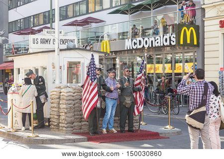 Berlin, Grmany - Sept 19, 2016: Tourist taking pictures and selfies at Checkpoint Charlie, famous Berlin Wall crossing point during the Cold War, on 19th of September, 2016 in Berlin, Germany.