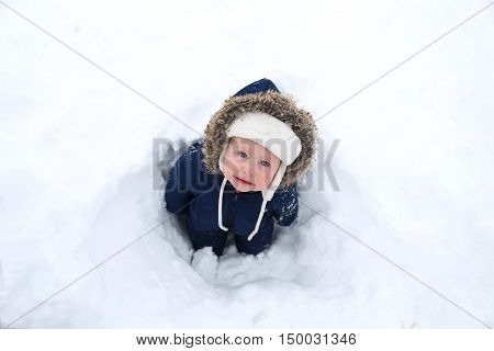A cold 10 month old baby is wearing a warm furry snowsuit and standing in a hole in the snow on a winter day.