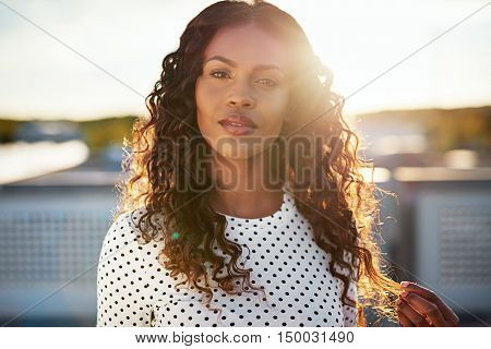 Dreamy young woman backlit by the rising sun standing on an urban rooftop playing with her gorgeous long curly hair as she stares at the camera
