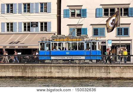 Zurich, Switzerland - 25 September, 2016: an old time tram, pedestrians and a flag of the Zurich Film Festival on the Limmatquai quay. Trams have been a consistent part of Zurich's cityscape since the 1880s when the first horse tram ran.