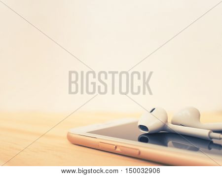 Close-up image of earbuds on top of smartphone and reflection on screen on wooden table with copy space. Cross process filter