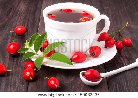cup with rose hip tea on a dark wooden background.