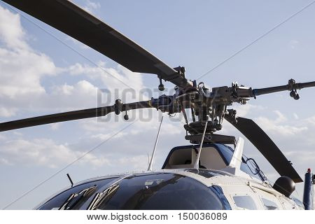 blades of a helicopter standing on land on a helipad