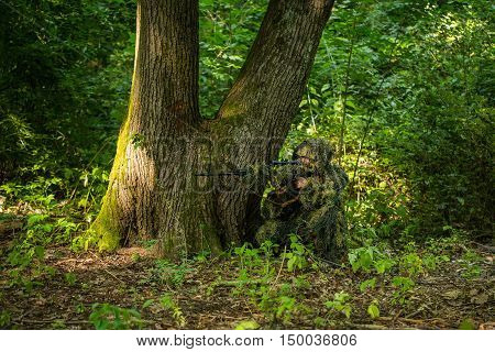Sniper soldier man in military ghillie suit camouflage with rifle in hands aiming target sitting in ambuscade near tree in forest