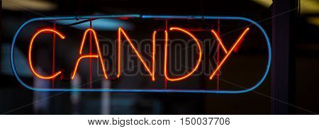 Neon candy sign on a window in the united states