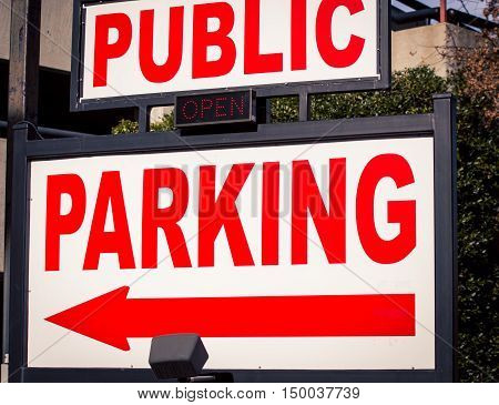 Red and white public parking sign with an arrow
