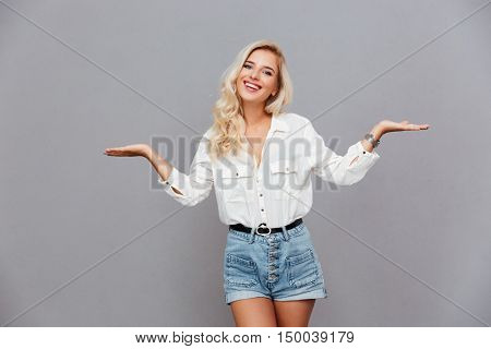 Portrait of a cheerful girl holding copyspace on the palms isolated on a gray background
