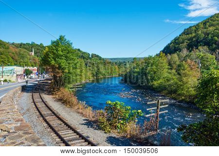JIM THORPE PENNSYLVANIA - SEPTEMBER 28: Railroad tracks along the Lehigh River lead into Scenic Jim Thorpe on September 28 2016 in Pennsylvania