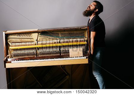 Bearded Man Trying To Move Wooden Piano