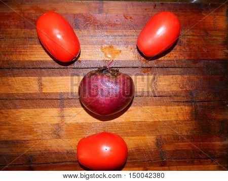 Three red tomatoes and purple beets are laid out in the form of face on a wooden board. Vegetables are funny.