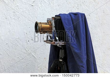 Old wooden camera on the background of the plastered walls