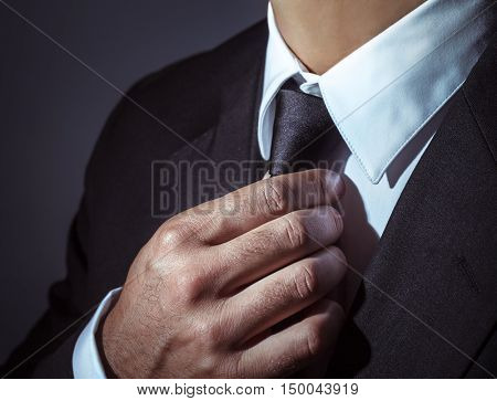 Closeup photo of a man wearing stylish black suit and tie over dark background, body part, men's fashion concept