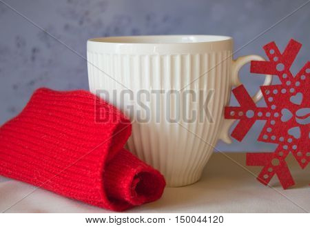 White mug and snowflake with a red knitted scarf. The Concept Of Christmas.