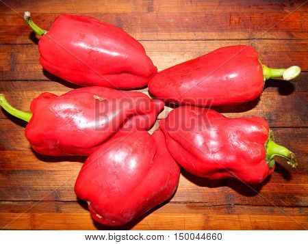 Five large red pepper washed and cooked for a vegetarian meal. Vegetables are laid out on a wooden board.