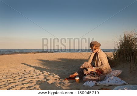 Beautiful view of ocean in autumn woman in knitted cardigan on the beach in autumn reading book