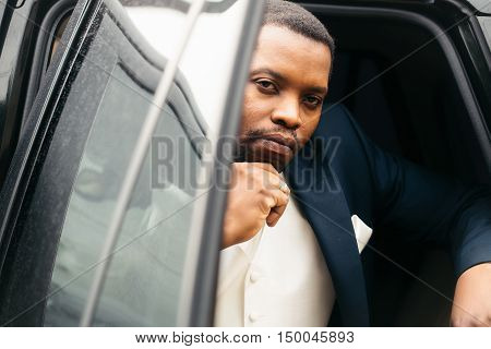 Handsome man african American groom in elegant suit with white tie and handkerchief pocket square for wedding ceremony sits in car