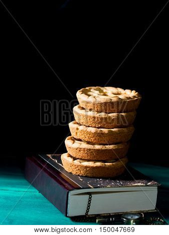 Shortcrust tartlets with peach jam stacked on a book on dark green and black background. Vertical image