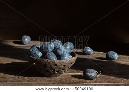 brown ceramic colander with plums plums in a clay colander plums on a brown background.