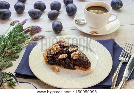 Plum cake on a white plate next to a cup of coffee plums lavender bouquet knife and fork on light wooden background. A piece of plum cake with coffee. Horizontal. Daylight.